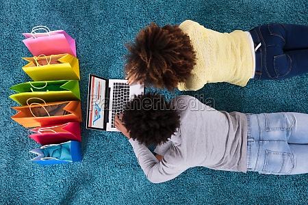 couple lying on carpet shopping online