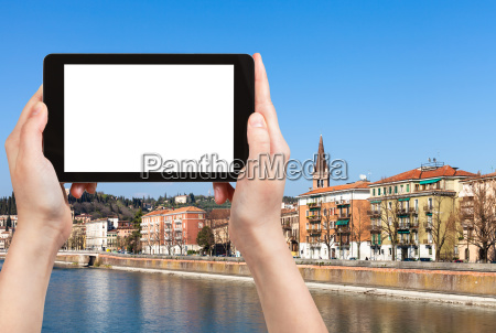 tourist photographs waterfront in verona town