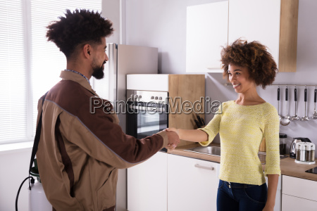 pest control worker shaking hands with