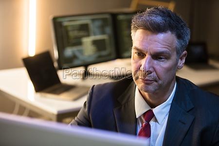 geschaeftsmann der an computer arbeitet