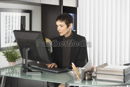 geschaeftsfrau die am schreibtisch arbeitet