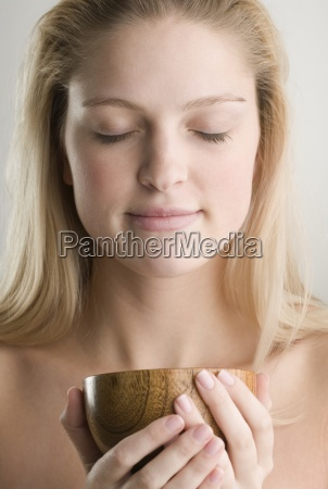woman meditating and holding wooden cup