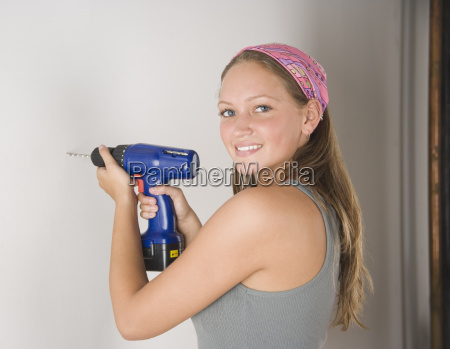 young woman using cordless drill on