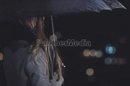 female outdoors in rainy night