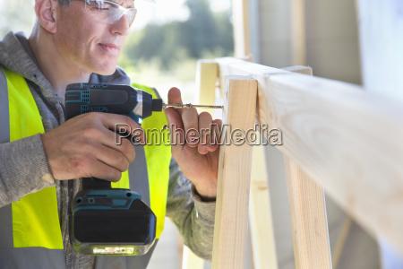 carpenter using power drill to screw