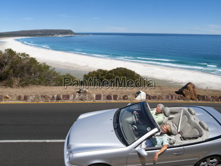 senior couple on holiday driving convertible