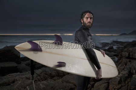 surfer with surfboard standing on rocks