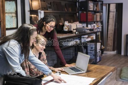 three women gathered around table in
