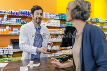 pharmacist explaining medicine to customer in