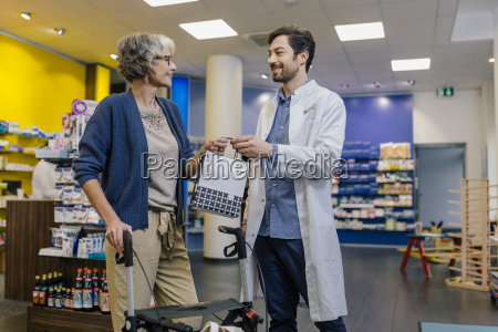 apotheker der dem kunden tasche mit