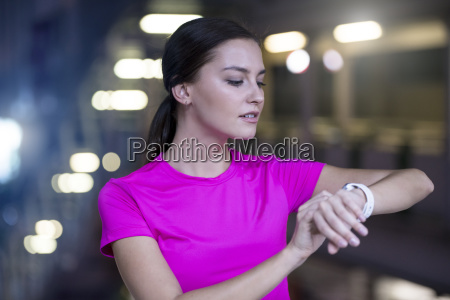 young woman in pink sportshirt checking