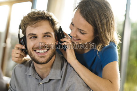 smiling woman putting on headphones on