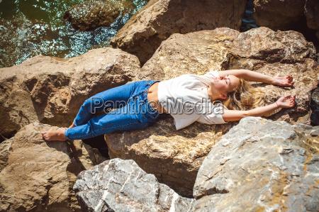 portraet junge frau auf steinen in