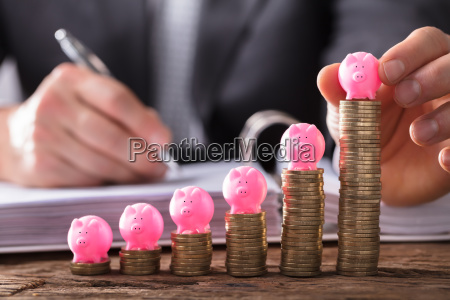 businessperson placing piggybank on stacked coins