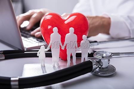 nahaufnahme von familienfiguren rotherzformform und stethoskop