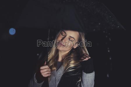 frau geniesst regnerische nacht