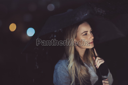 pensive woman outdoors in rainy night