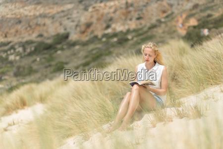woman reading book enjoying sun on