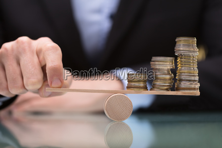 businessperson balancing stacked coins on seesaw