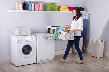 frau die nahe waschmaschine mit korb