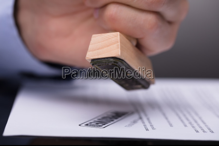 businessperson stamping document