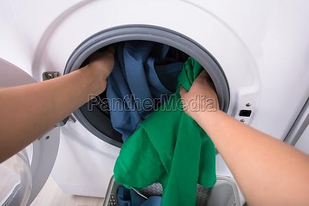 woman putting clothes in washing machine