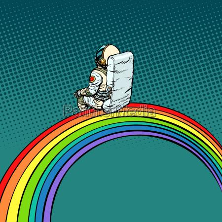 astronaut sitzt auf einem regenbogen