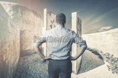 schwierigkeiten und herausforderungen geschaeftsmann vor labyrinth