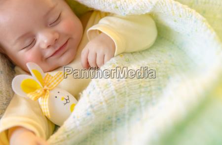niedliches baby schlaeft mit osterdekoration