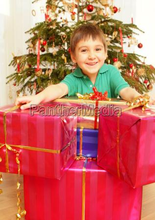kleiner junge mit weihnachtsgeschenken unter dem
