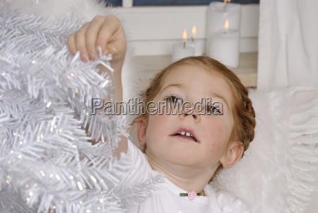 kind schmuckt einen weissen weihnachtsbaum