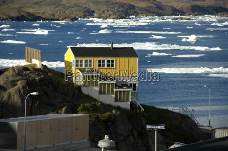 gelbes haus uberm fjord mit packeis