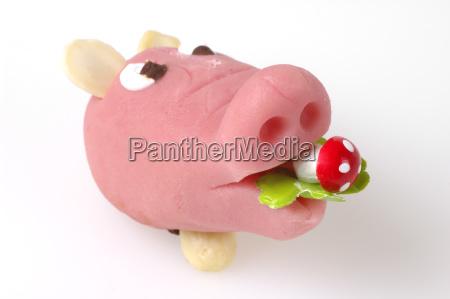 glucksschwein aus marzipan vor weissem hintergrund