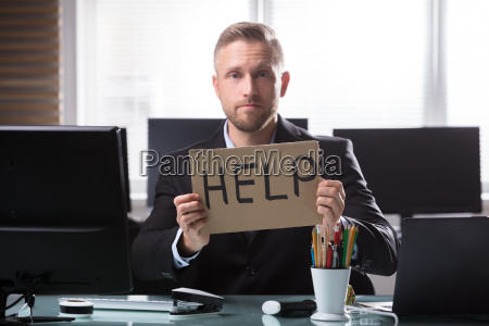 businessman holding cardboard with help text