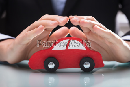 persons hand protecting red car