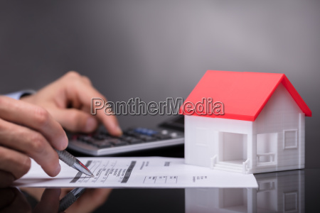 businessperson calculating invoice besides house model