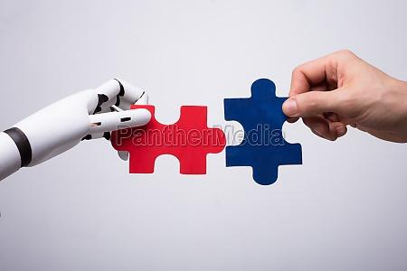 robot and human hand holding jigsaw