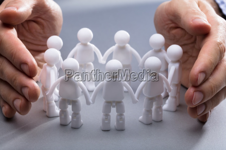 die hand der person die miniaturmenschfiguren