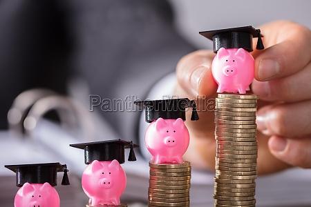 businessperson placing piggybank with graduation cap