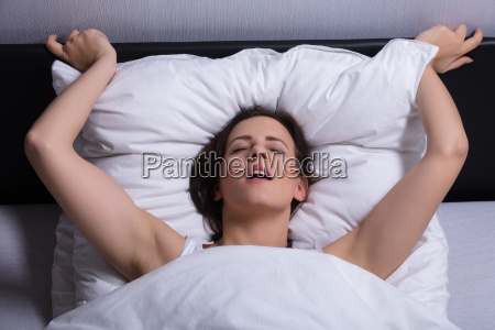 young woman in bed getting orgasm