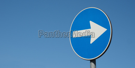 direction arrow sign over blue sky