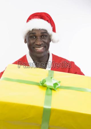 dunkelhautiger weihnachtsmann mit geschenk
