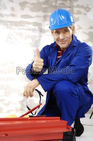 handwerker mit schutzhelm kniet vor einem