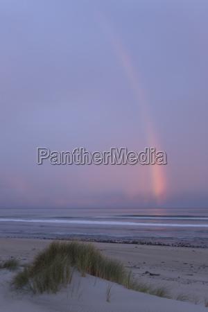 regenbogen an der westkuste im abendlicht