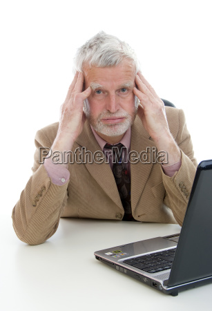 elderly overworked businessman with laptop