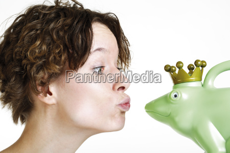 young woman is kissing frog konig