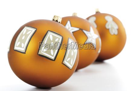 drei goldene christbaumkugeln mit weihnachtsmotiven