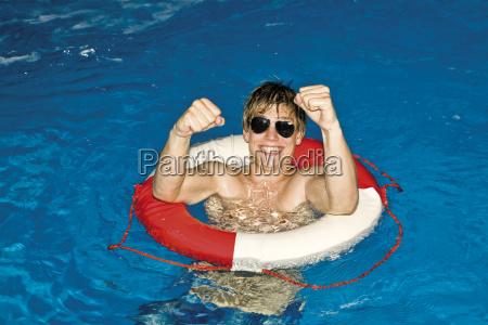 junger mann im pool mit sonnenbrille