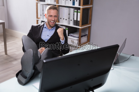 excited businessman looking at computer