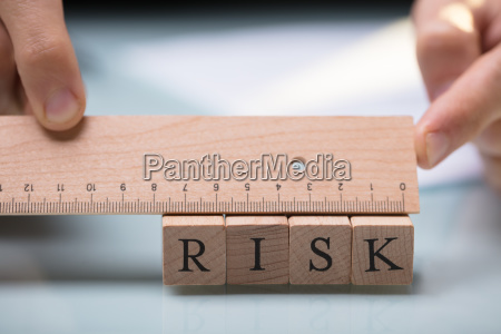 businessperson measuring risk blocks with ruler